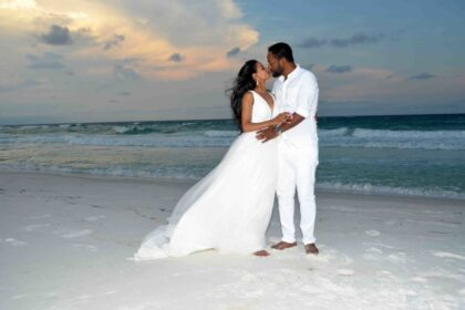 A newly married couple embracing on the beach.