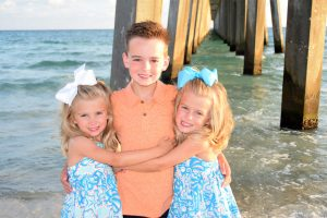 boy with twin sisters smiling by the pier in PCB