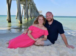 couple on the beach under the pier