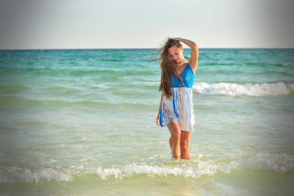 Girl in sun dress getting her senior portrait taken ankle deep in water on Panama City Beach.