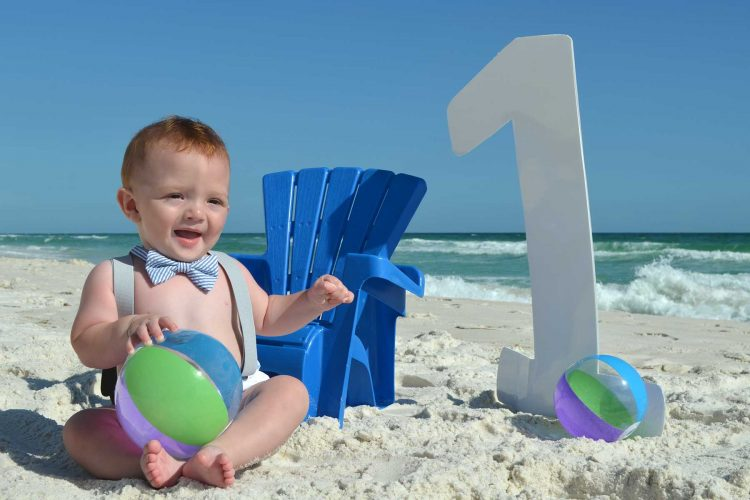 Little boy getting his birthday photo on the beach with a number 1