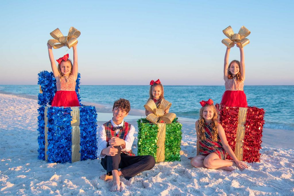 kids posing with holiday presents for their beach photos