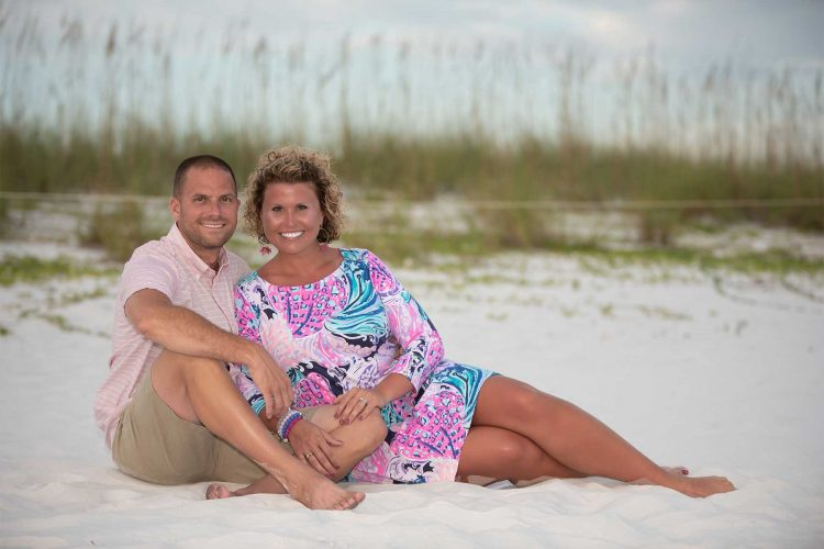 Couple smiling lounging on the beach with sea oats behind them.