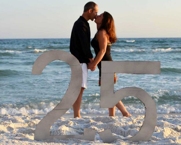 couple kissing with a 25 anniversay sign in front of them on Panama City Beach.