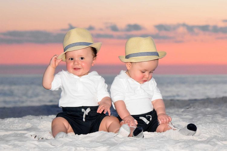 baby boys getting photographed on the beach at sunset