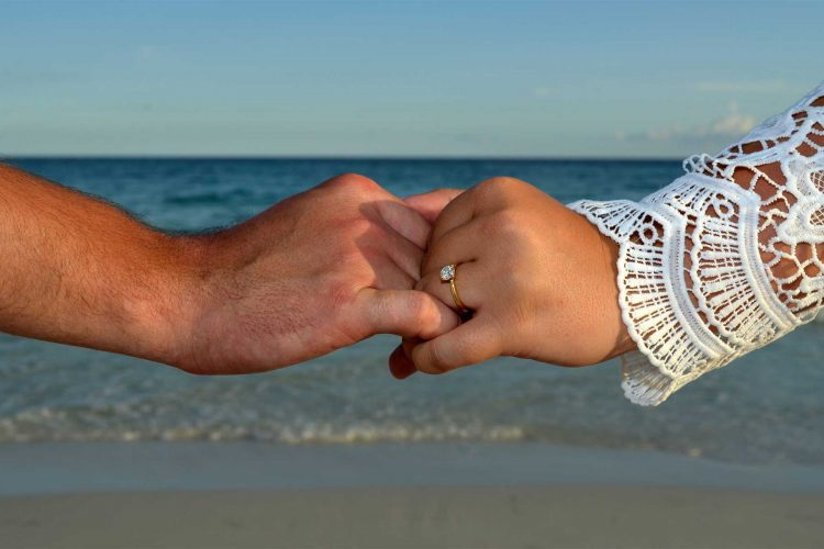 Closeup of couple holding hands with engagement ring visible