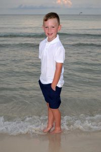 boy standing in waves at sunset