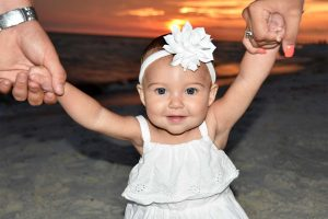 Baby with arms up. We take sunset family photos in Panama City Beach.