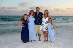 smiling family on Panama City Beach, FL, with waves in the background