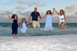 family jumping in the air for photographer