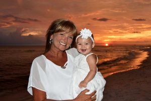 Woman with baby in front of beautiful sunset. We also take sunset photos in Destin, Fort Walton Beach, and Miramar Beach, FL.