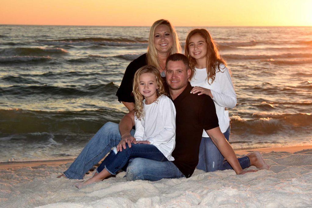 A family getting their sunset beach photos by our beach photographer