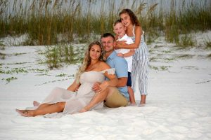 family posing with sea oats behind them