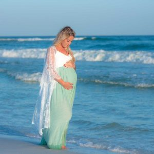 woman walking through the water in her sunset maternity photo