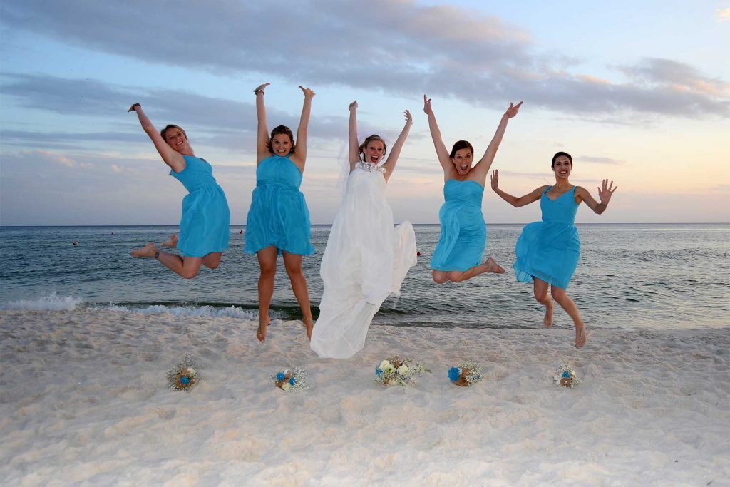 Bride and bridesmaids jumping in the air on the beach