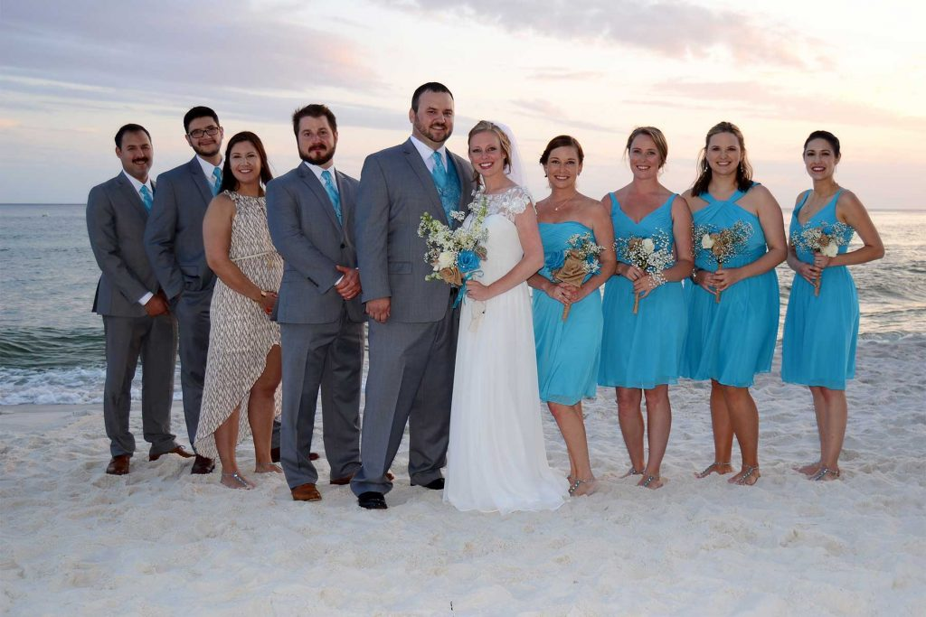A wedding party on the beach at sunset.