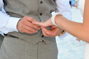 The groom putting the ring on the bride's finger during their beach wedding.