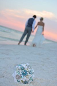 This photo shows the bride and groom walking down the beach towards the sunset. The bouquet is in the foreground.