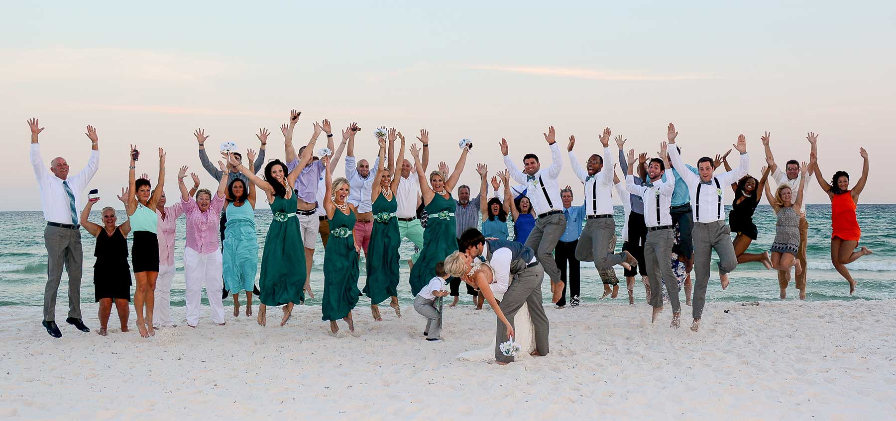 Photo of large wedding party at Panama City Beach.. Jumping in the air and having fun.