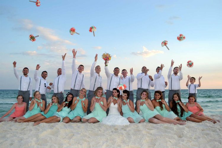 An action photo of the wedding party posed on the beach in front of a beautiful sunset.