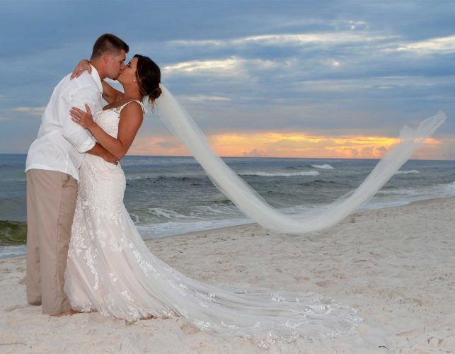 Our Panama City Beach wedding photographer captured this beautiful sunset wedding photo just as the breeze caught the bride's veil