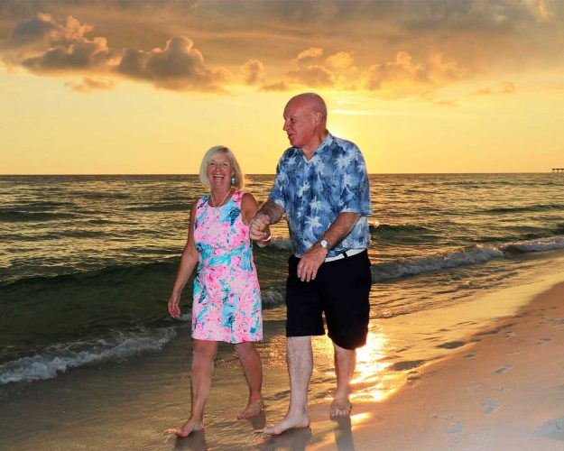 Older couple walking on the beach with a beautiful sunset behind them