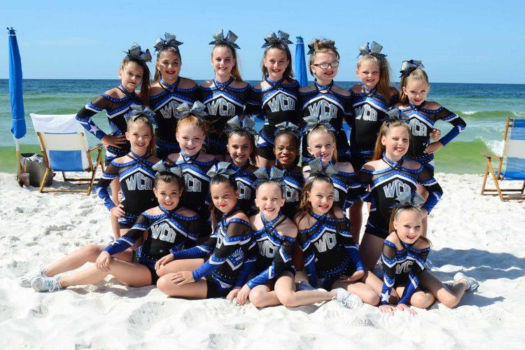 Cheerleading squad getting their team portrait at the beach