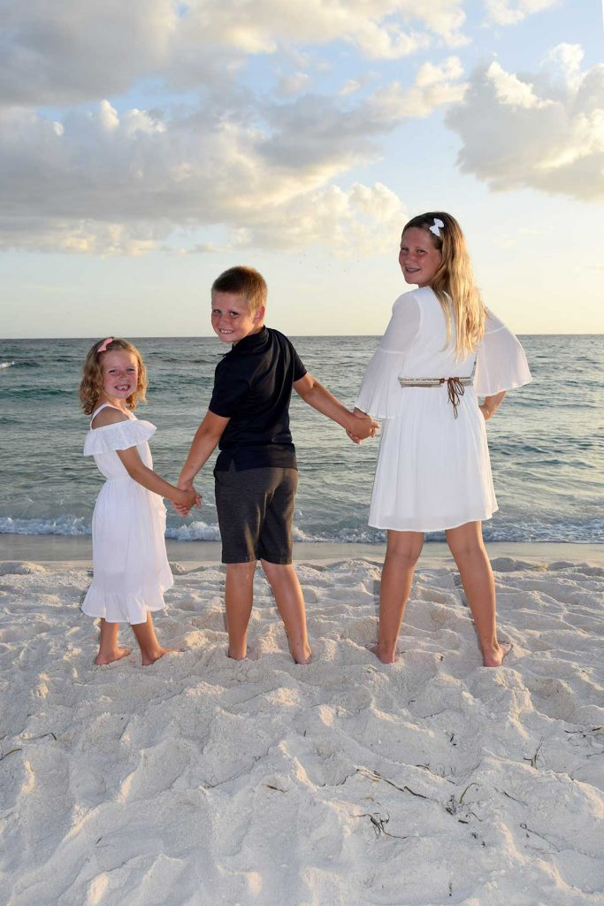 kids with backs to photographer in sunset beach photo