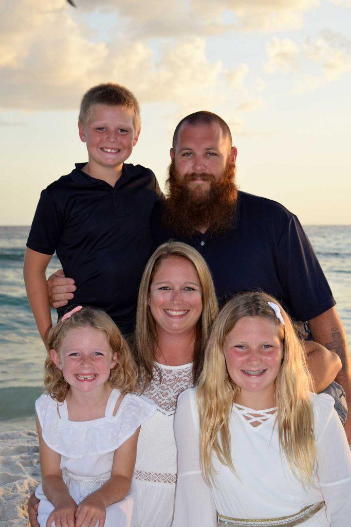 Family smiling in stunning sunset beach photo in Panama City Beach