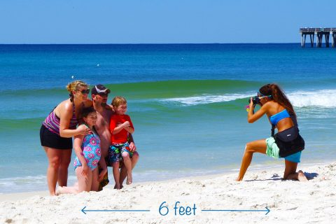 One of our photographers, April, taking family beach photos. Visit PCB this summer for a safe, fun vacation.