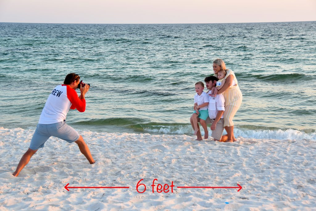 Our beach photographer snapping vacation pics for a family in Panama City Beach, FL. He is six (6) feet away.