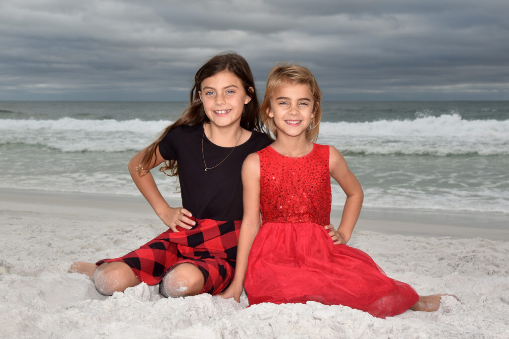 Two girls sitting on sand on Destin beach with waves behind them.
